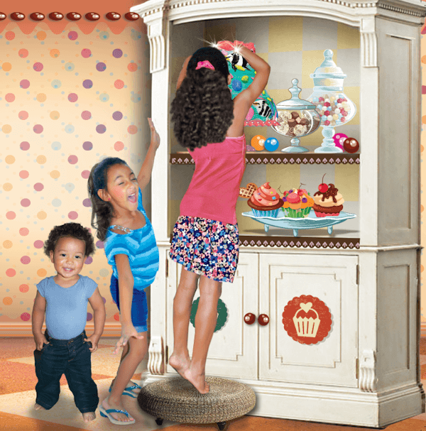 3 children smiling in front of a sweets cabinet